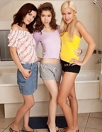 Three Cute Teenage Lesbians Helping Each Other To Get Naked And Naughty In A Bathroom.