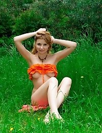 Stunning Curly Haired Teen Poses In The Tall Grass In A Summer Dress, Showing Off Glimpses Of Her Na