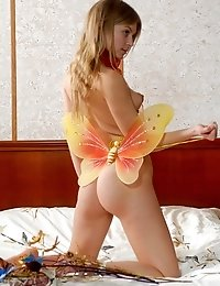 Astounding Nude Angel Wearing Only Butterflys Wings Is Playing On The Couch With Flowers And Little