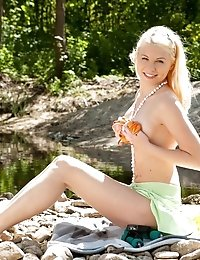 Amazing Blonde Cutie In A Handsome Necklace On The Neck Taking Off Clothes On The Beach.